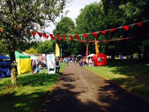 A path through the park is lit by sunshine. Red bunting hangs across the path and there are giant flags on either side.