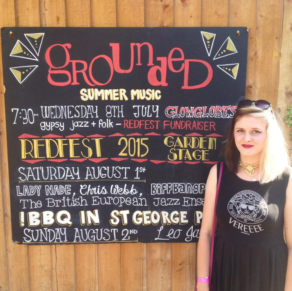 A young blonde woman stands in front of a blackboard that reads: Grounded summer music: 7.30 Wednesday 8th July Glow Globes gypsy jazz folk Redfest fundraiser; REDFEST 2015 GARDEN STAGE Saturday August 1st Lady Nade, Chris Webb, BiffBangPow, The British European Jazz Ensemble: BBQ IN ST GEORGE PARK: